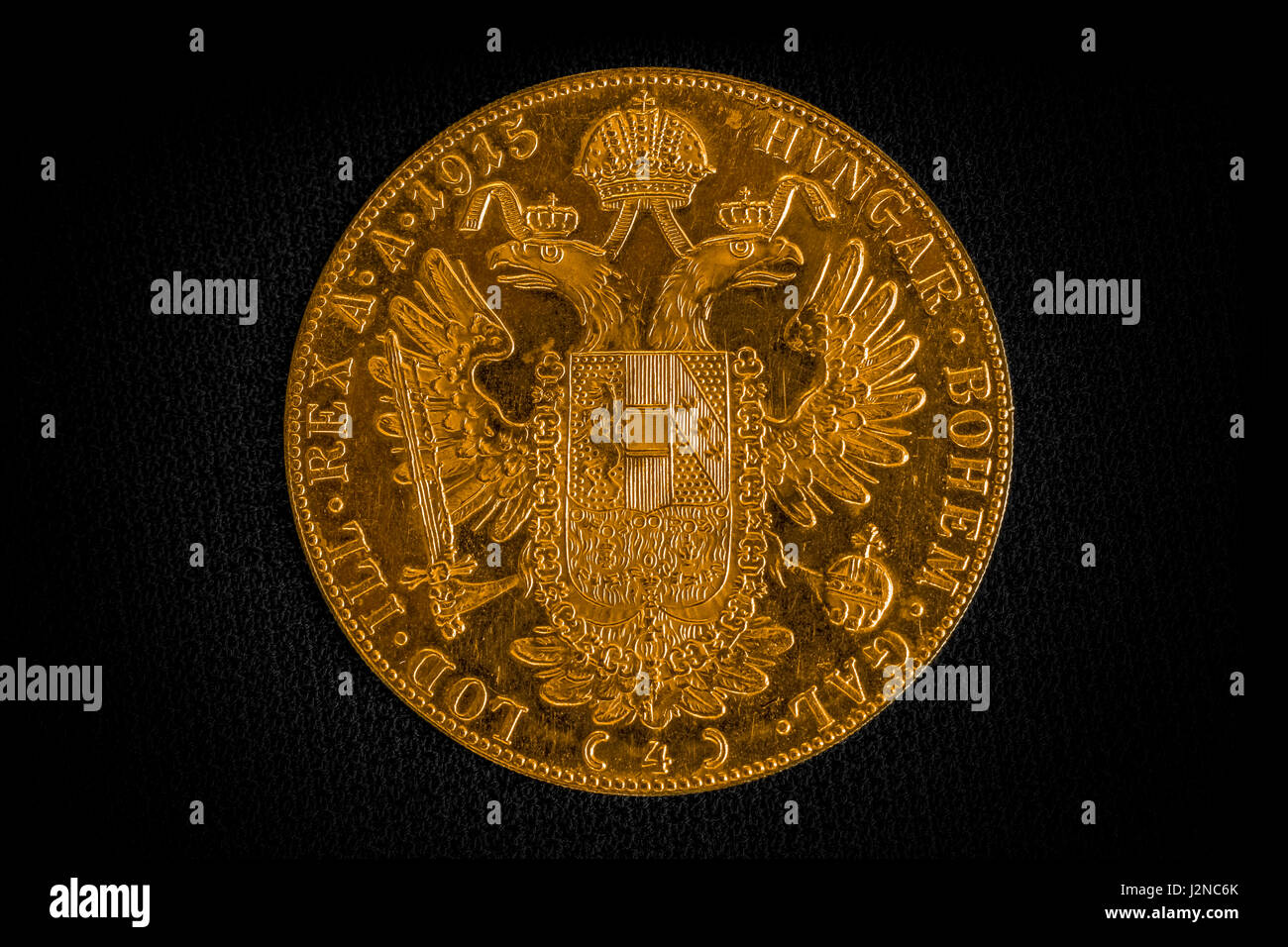 Close-up view of Austria-Hungary thaler, revers of golden coin-ducat from 1915 with Kaiser Franz Joseph I on dark - Stock Image