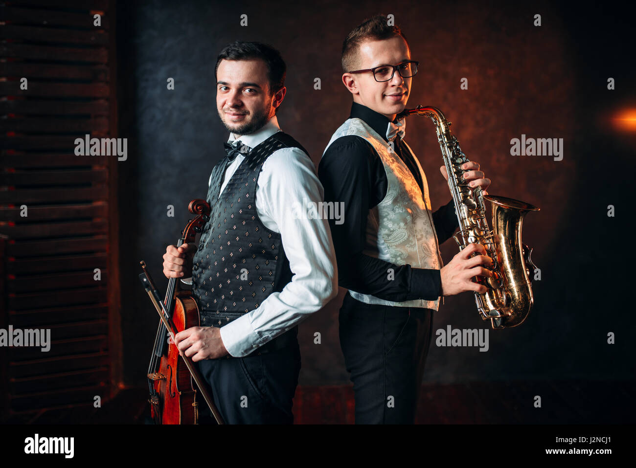Saxophonist with sax and violinst with violin musical duet. Jazz-man and fiddler - Stock Image