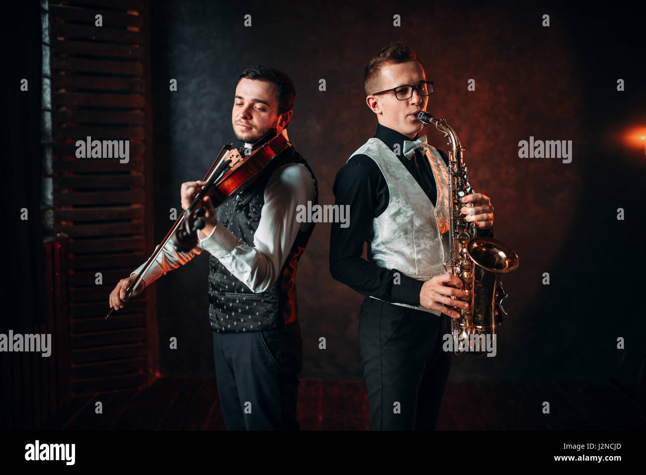 Saxophonist and violinst playing classical melody, musical duet. Jazz-man and fiddler - Stock Image