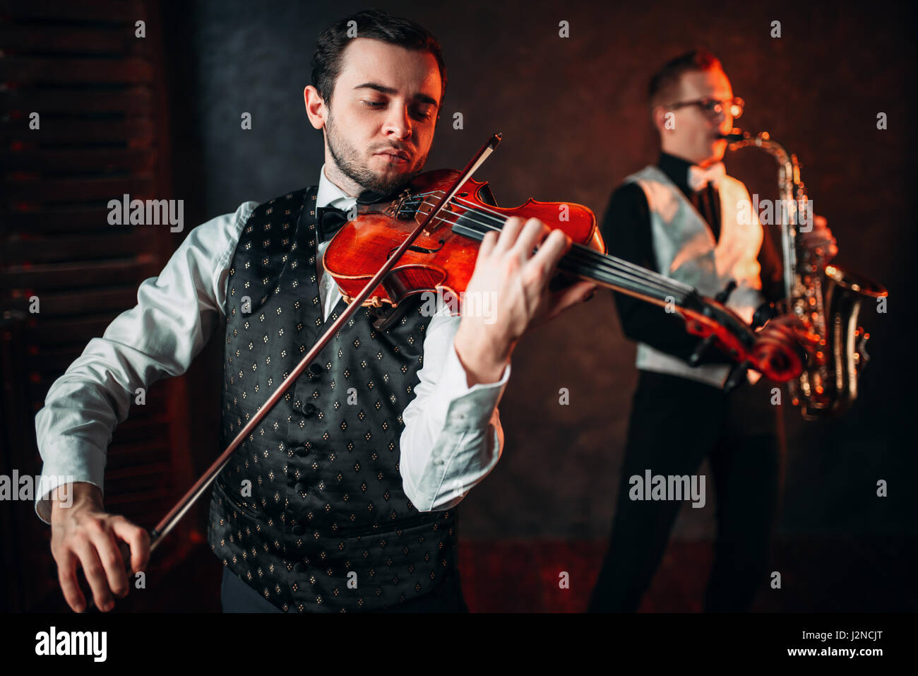 Jazz man and violinst, classical musical duet. Sax and fiddle music players - Stock Image