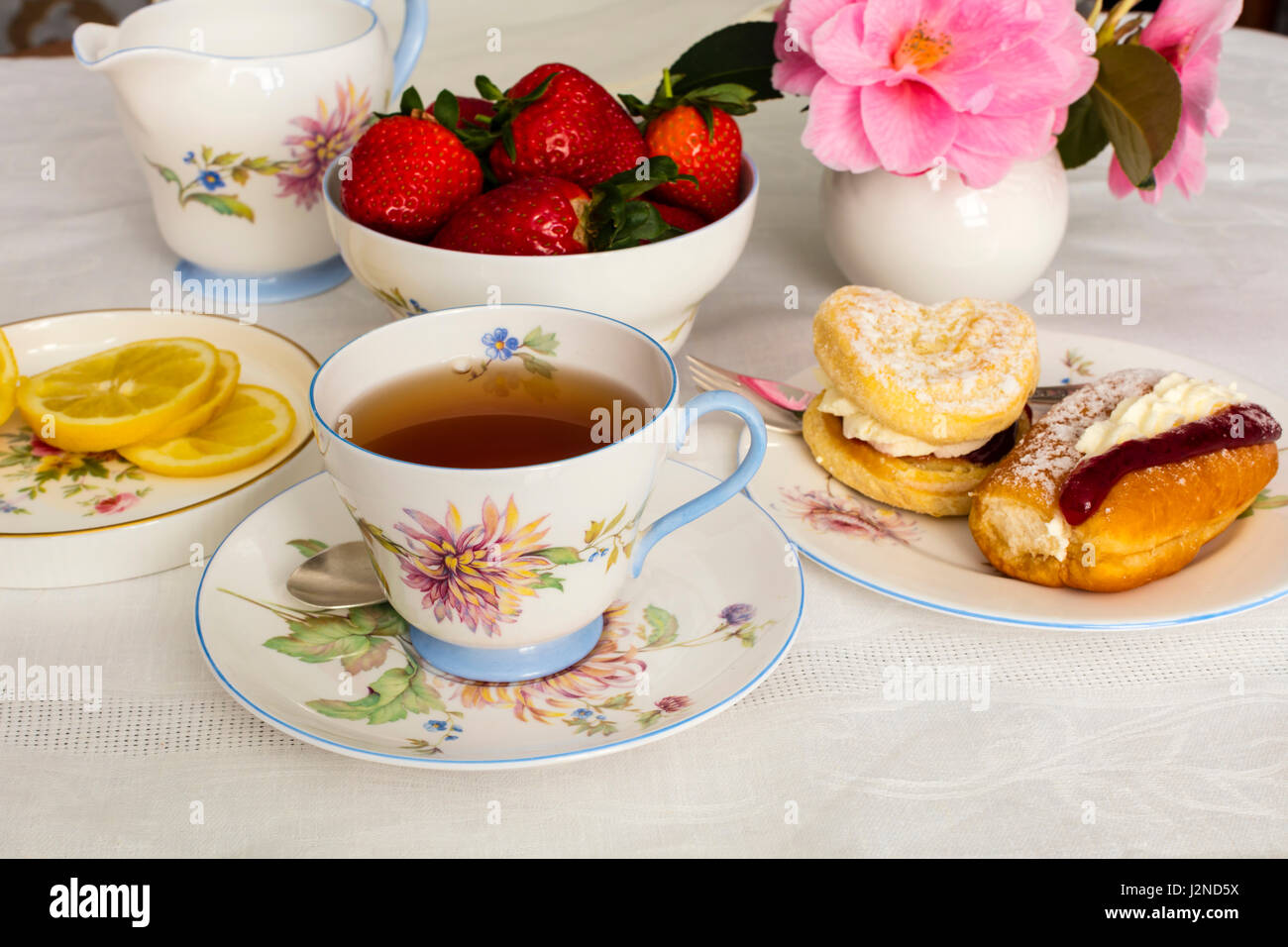Cup of tea served in a vintage fine china tea cup with cream cakes. - Stock Image