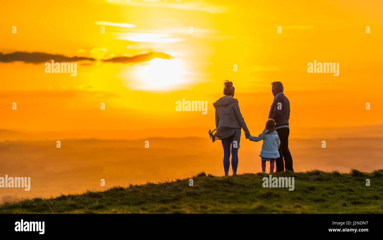 Small family standing on a hill watching the sunset while holding hands. Togetherness concept. Always concept. Closeness - Stock Image
