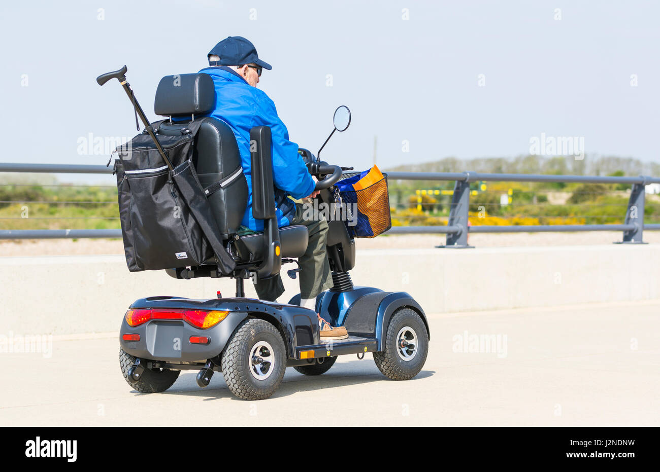 Elderly man on a path in an electric mobility scooter for disabled people. - Stock Image