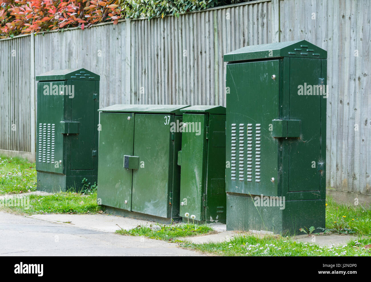 BT green PCP telephone cabinets and ECI 128/256 FTTC cabinets on a street in the UK. - Stock Image