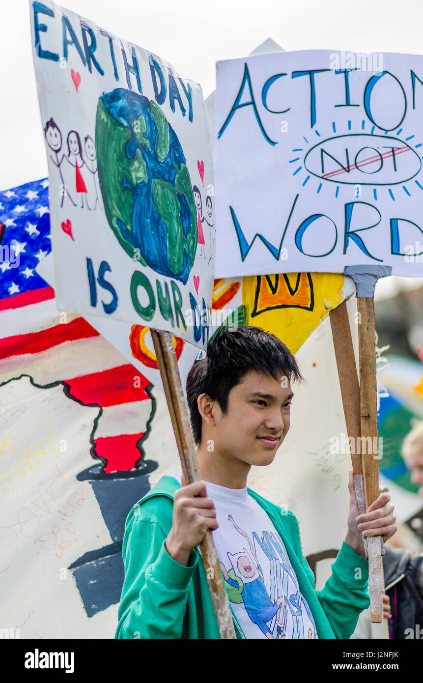 Teen with signs at  Earth Day Parade, Vancouver, British Columbia, Canada Stock Photo