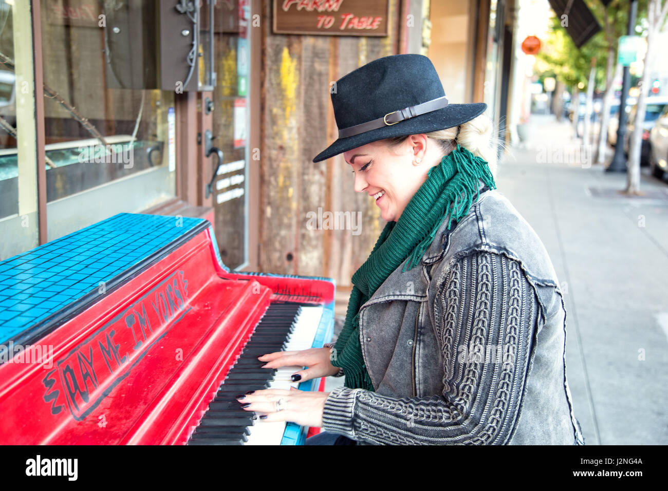 A fashionable 30-something woman plays piano on a city street. - Stock Image
