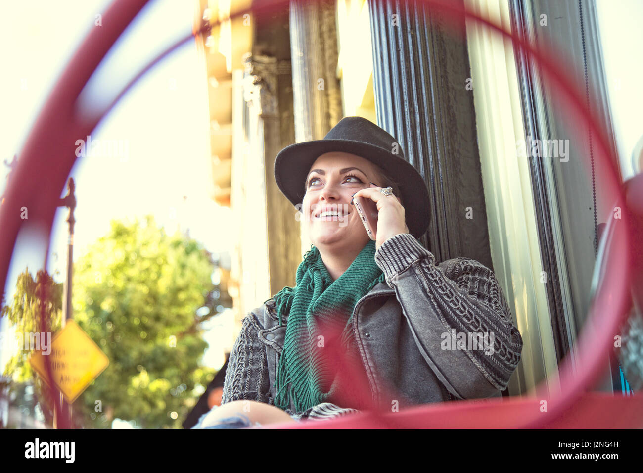A fashionable 30-something woman smiles and laughs while using a mobile device. - Stock Image