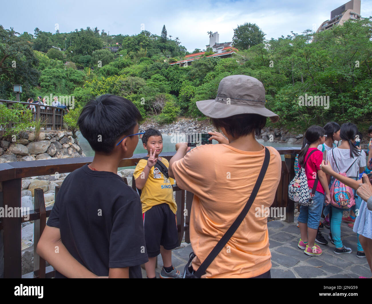 Xinbeitou, Taiwan - October 06, 2016: Taiwanese family take a picture in a background of the natural hot springs - Stock Image