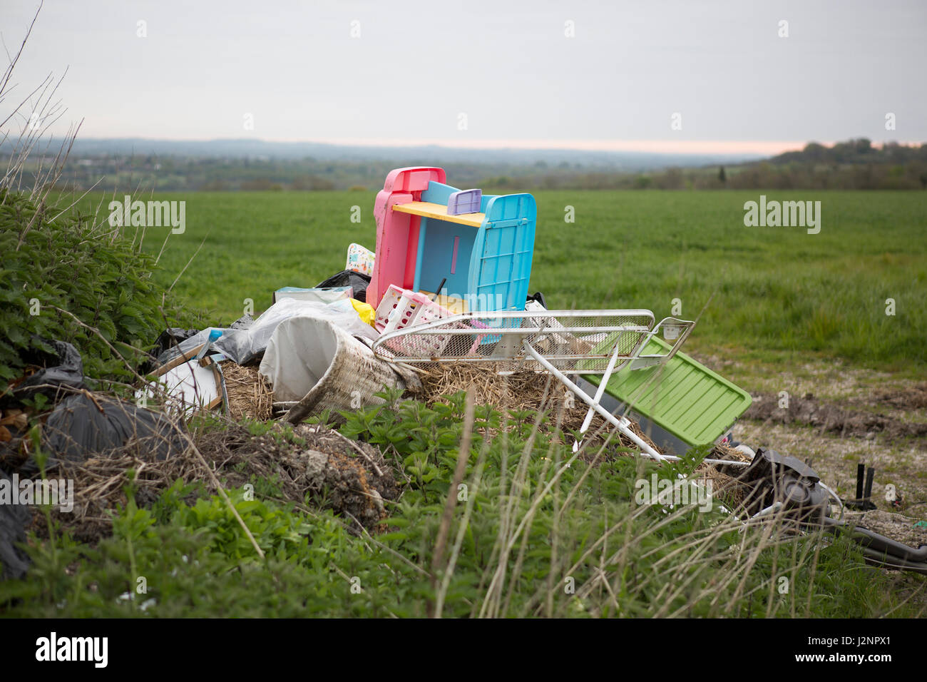 Waste dumped in the countryside in the countryside, an illegal social issue, fly tipping causing environmental pollution - Stock Image