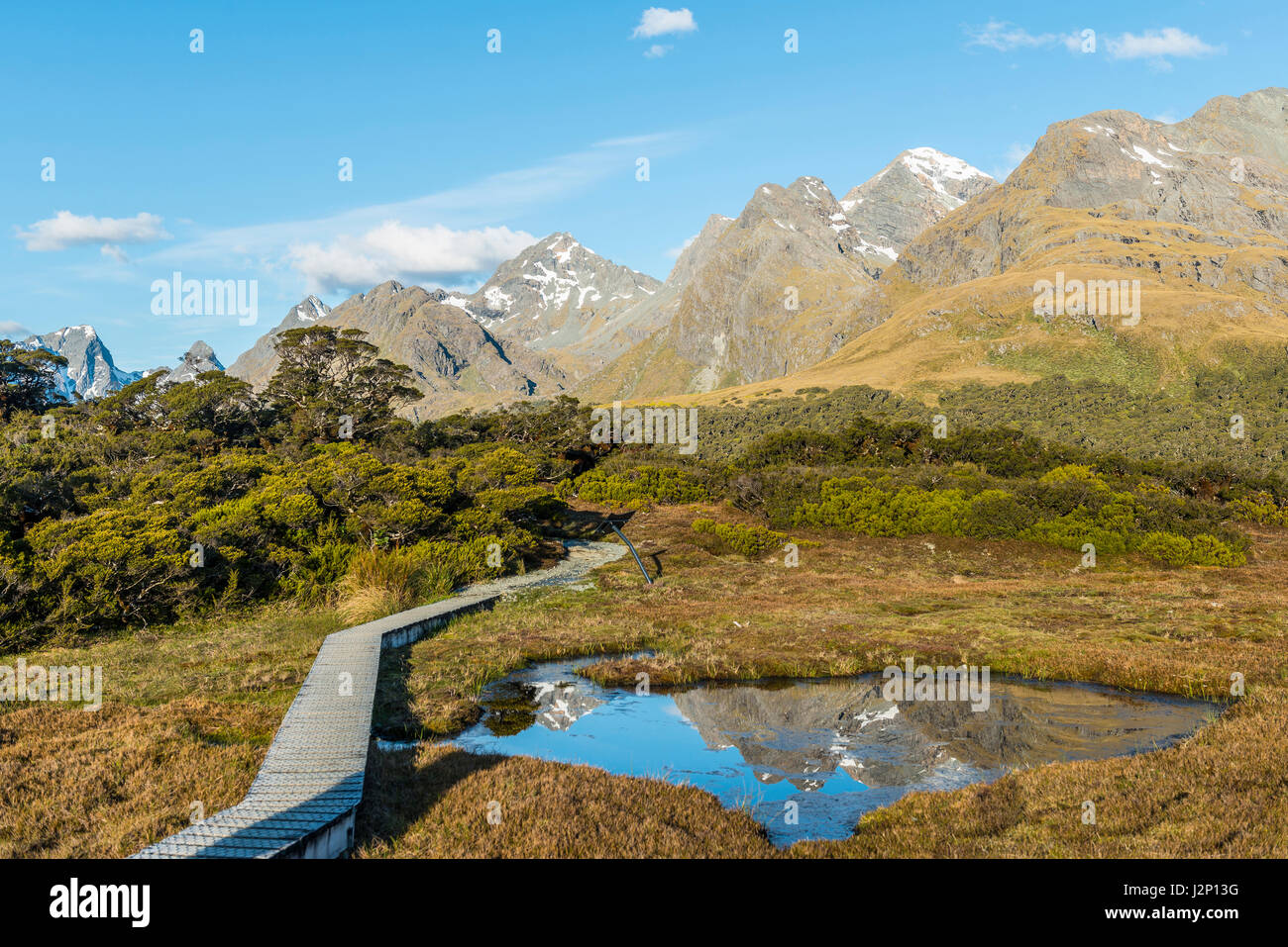 Bridge over Hochmoor, mountain lake with reflection of the Ailsa Mountains, Key Summit Track, Fiordland National - Stock Image
