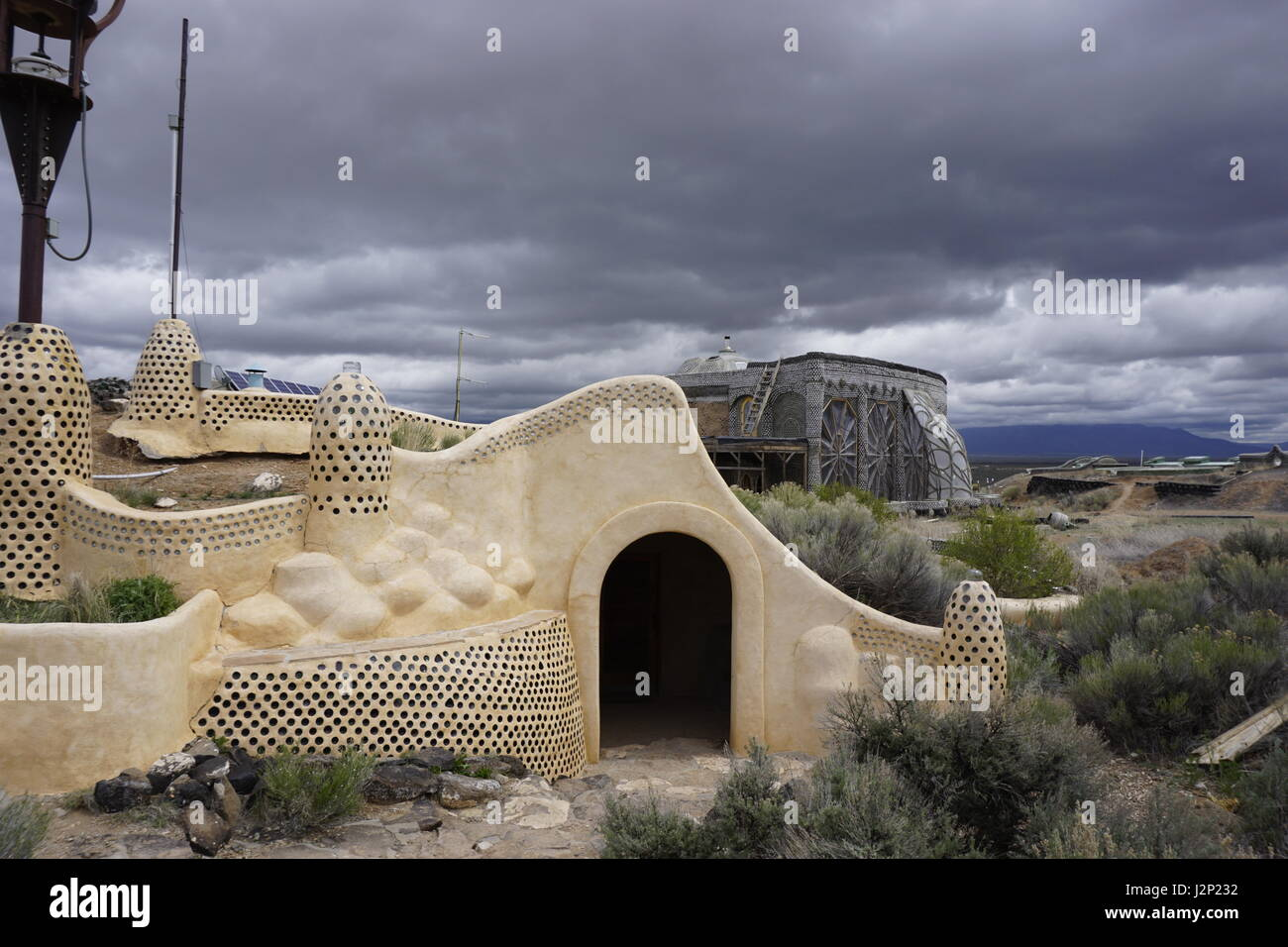 Storm clouds roll past two off-grid, sustainable earthship structures at the Earthship Biotecture visitor center - Stock Image