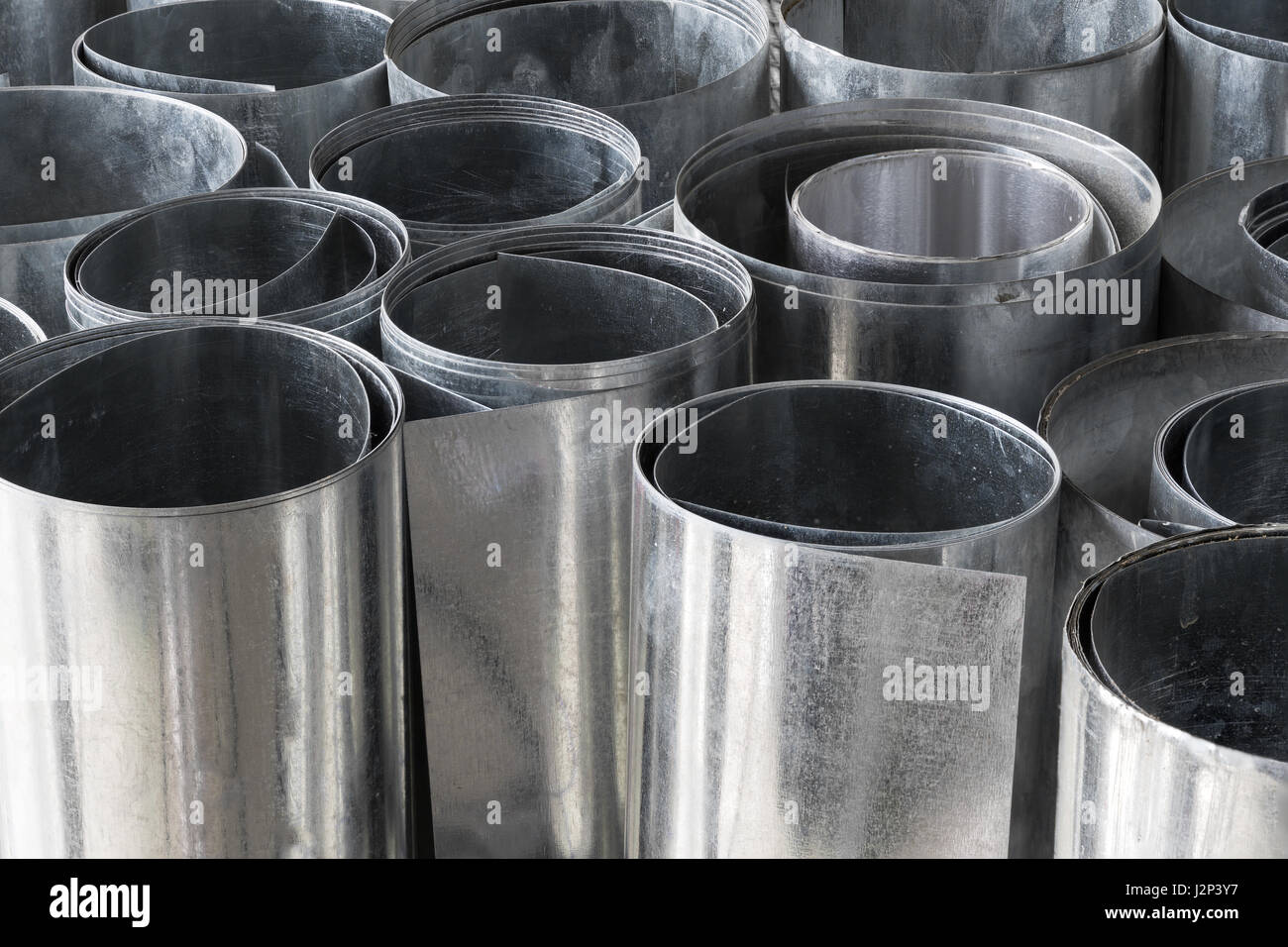 Rolls of flat galvanized metal sheets, building material - Stock Image