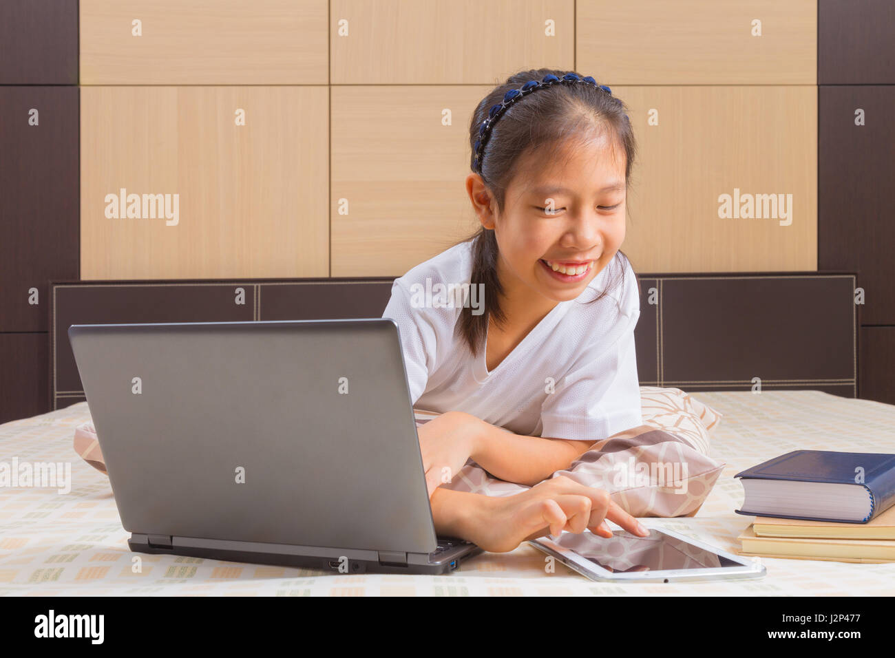 Happy Asian female teenager using technology, interacting with moblie computer tablet device in her bed Stock Photo