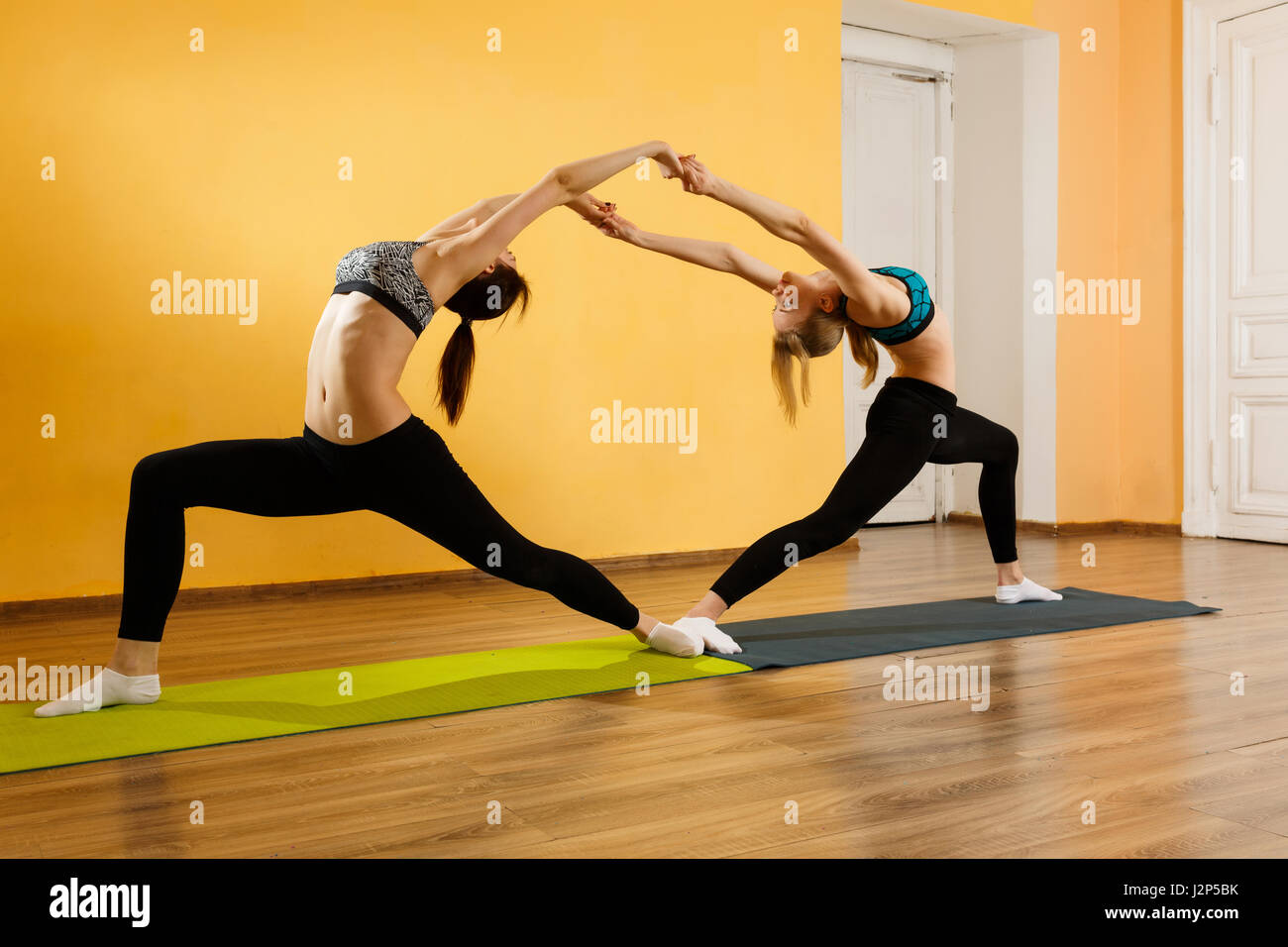 Two athletes doing stretching exercises - Stock Image
