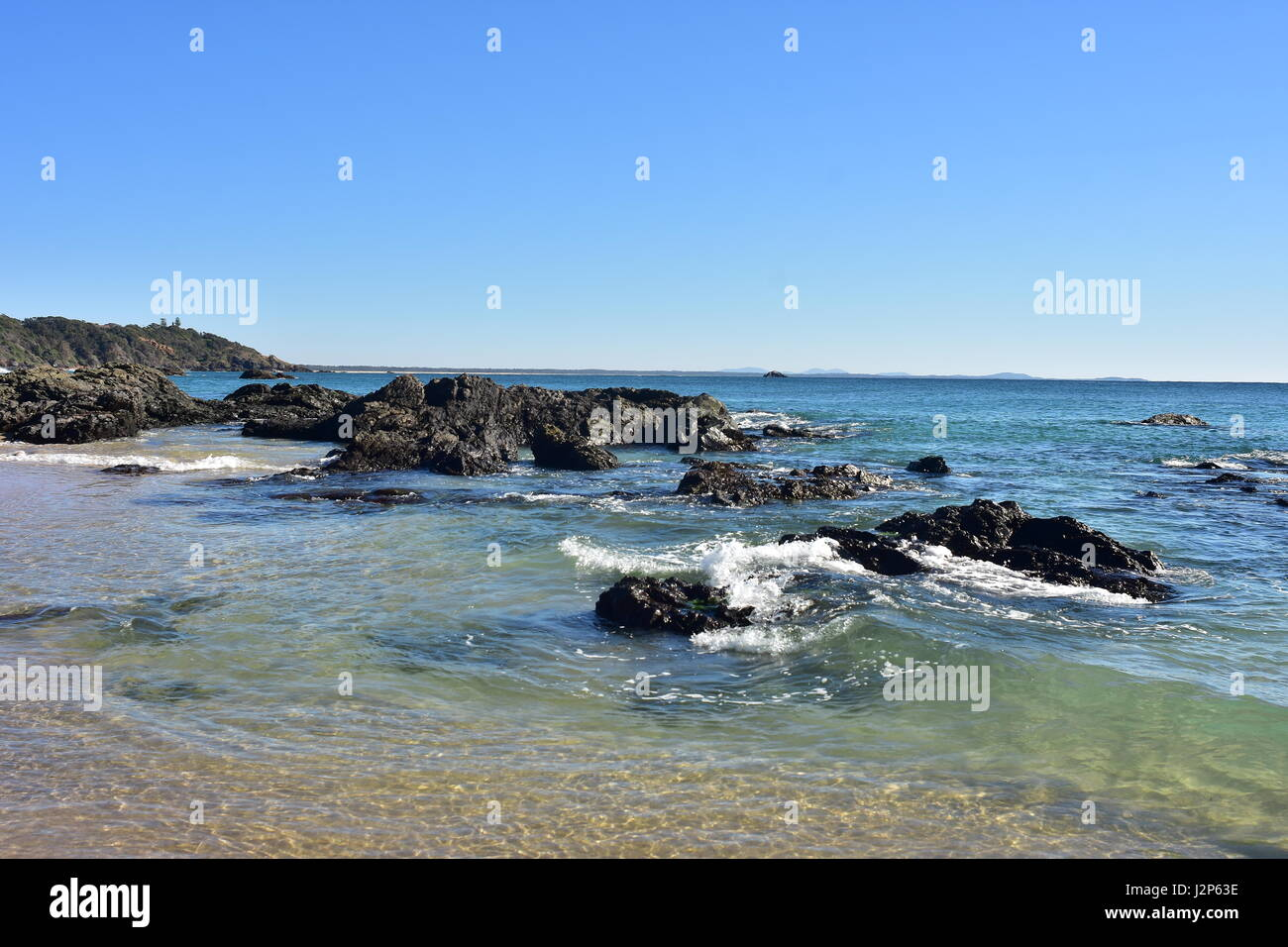 Sandy beach with dark rock formations on Nobby Beach in Port Macquarie. - Stock Image