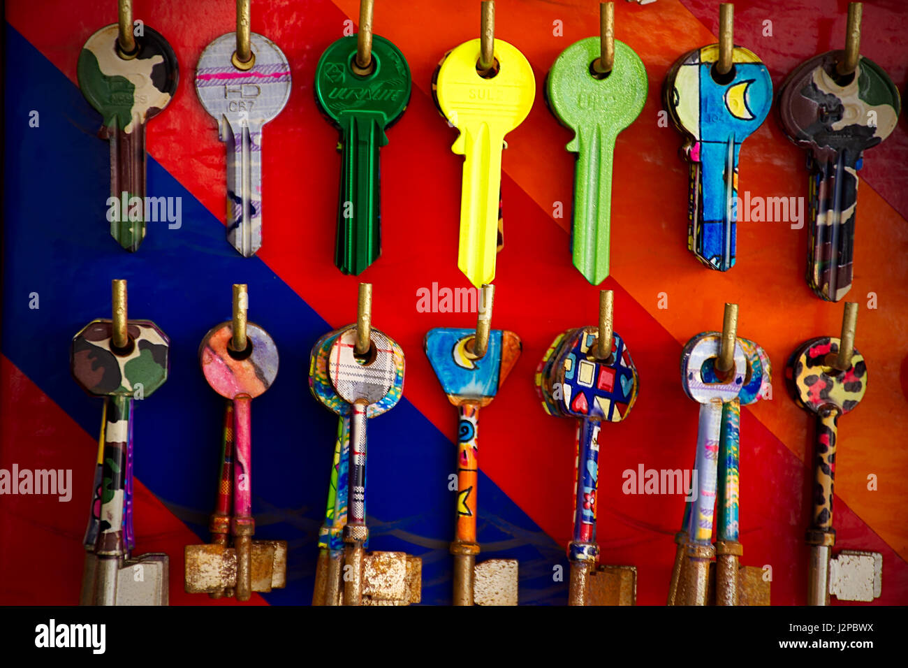 Old rusty , colourful keys hanging on hooks in key cutting service point.Vibrant colors abstract.Locksmith Uk. - Stock Image