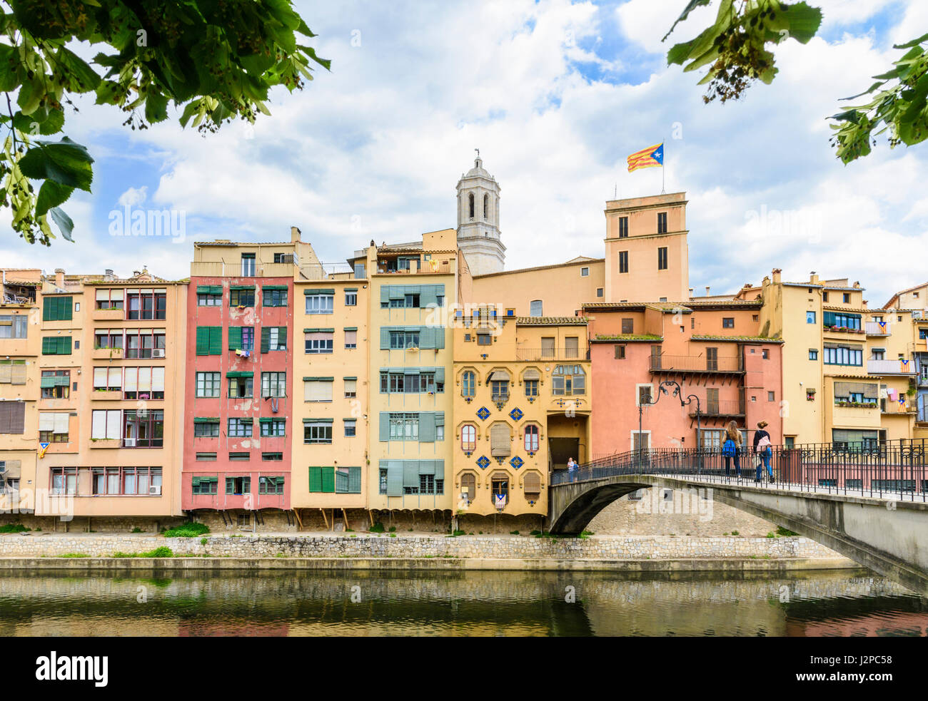 People walking on Pont d'en Gómez bridge over the River Onyar with the cathedral belltower towering over - Stock Image