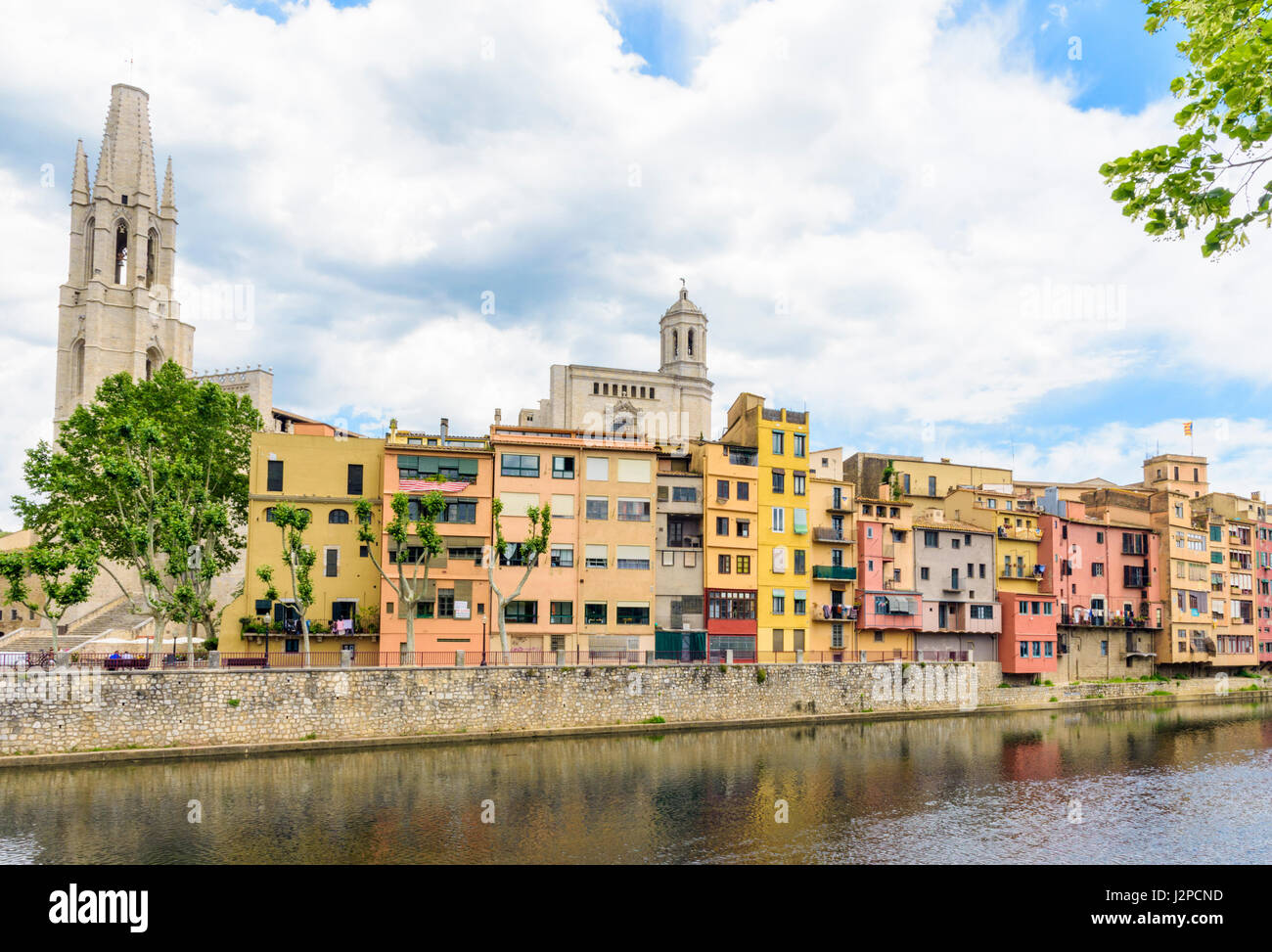 Banks of the River Onyar with the Basilica de Sant Feliu and Cathedral belltower towering over the old town hanging - Stock Image