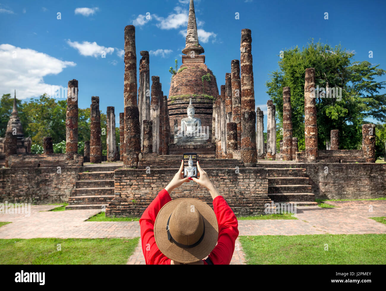 Tourist Woman in red costume taking a photo of ancient Buddha with her smartphone in Wat Sa Si of Sukhothai Historical - Stock Image