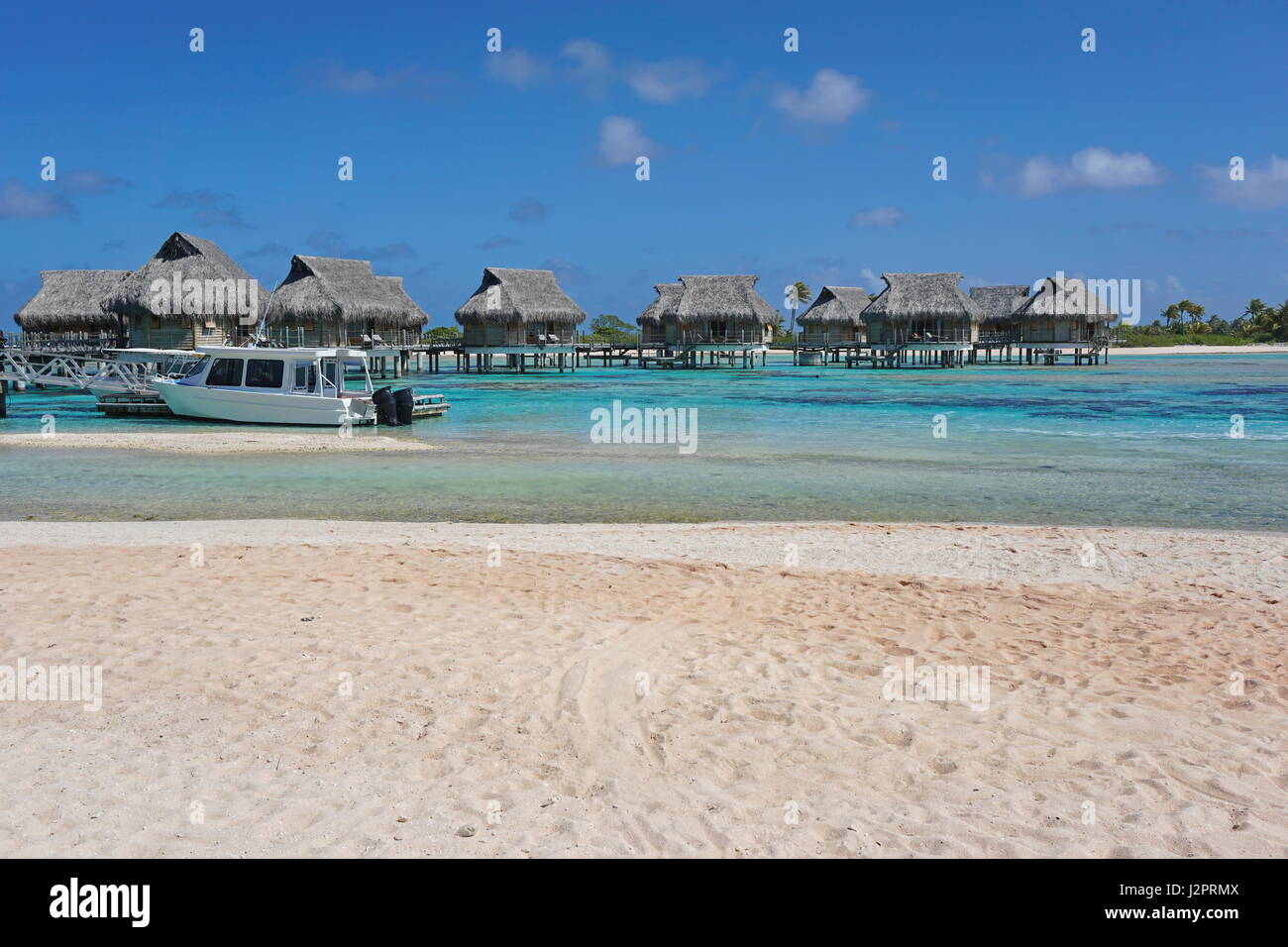 Tropical overwater bungalows in the lagoon seen from a sandy beach shore, atoll of Tikehau, Tuamotu, French Polynesia, - Stock Image