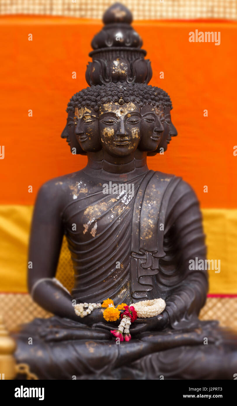 Close-up of meditate Buddha statue with multi faces in soft-focus in the orange background - Thailand - Bangkok - Stock Image