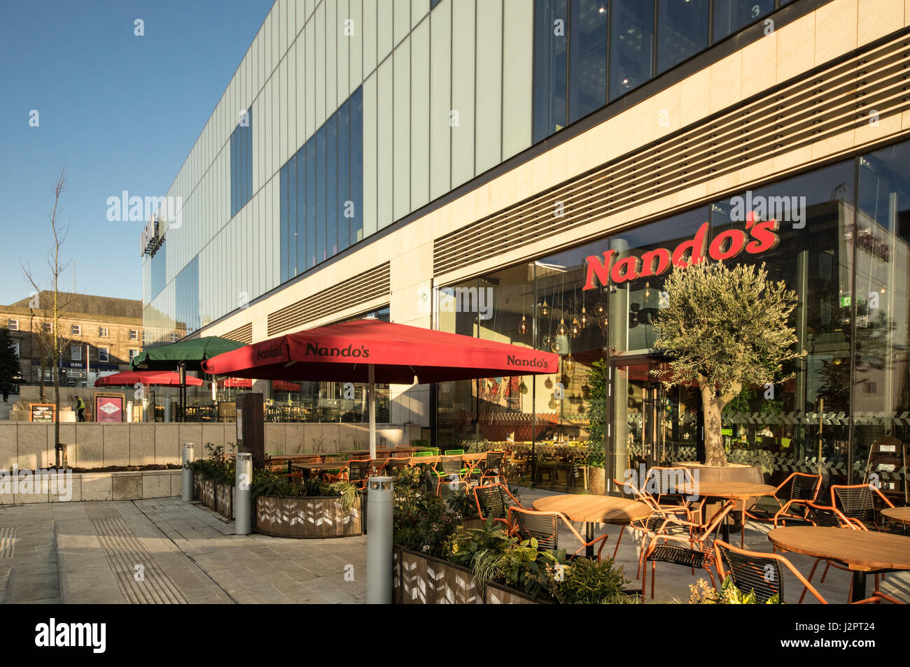 Nando's at Oldham Town Centre leasure complex with the cinema complex at the Oldham Town Hall behind it - Stock Image