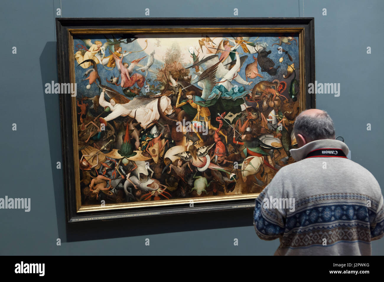 Visitor in front of the painting 'The Fall of the Rebel Angels' by Dutch Renaissance painter Pieter Bruegel the Stock Photo