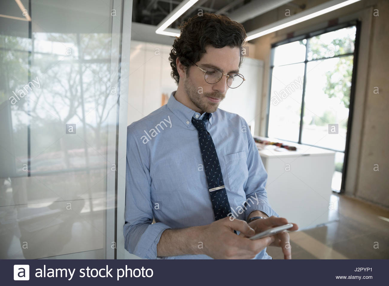 Businessman texting with smart phone in conference room - Stock Image