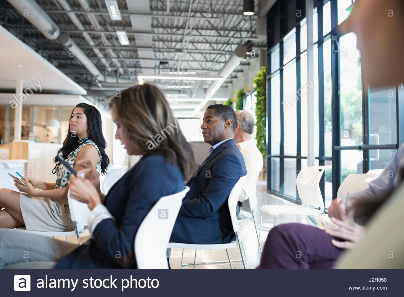 Business people listening in conference audience - Stock Image
