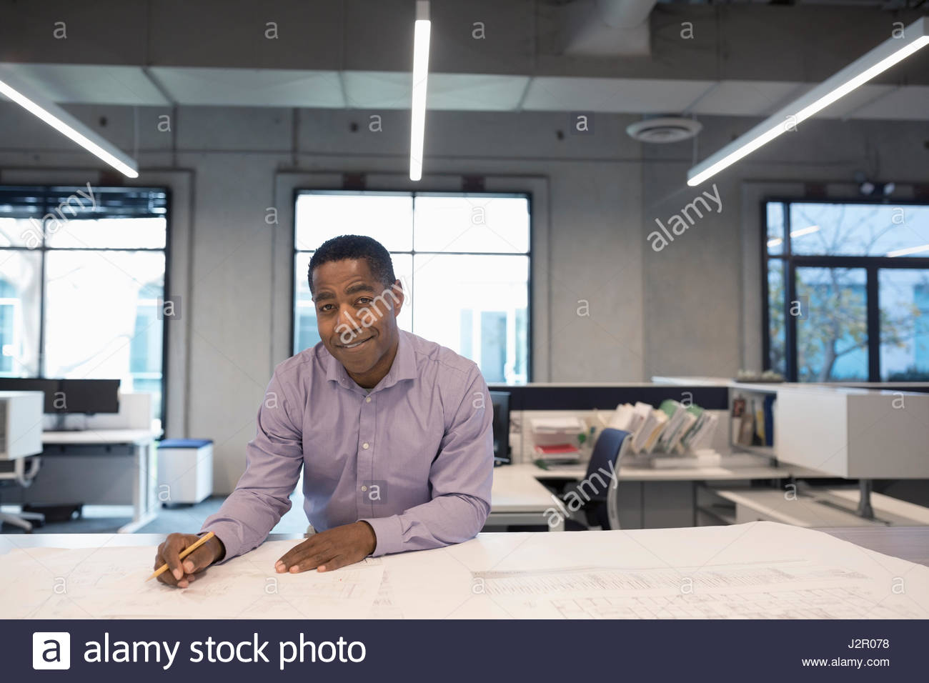 Portrait confident African American architect drafting and reviewing blueprints in office - Stock Image
