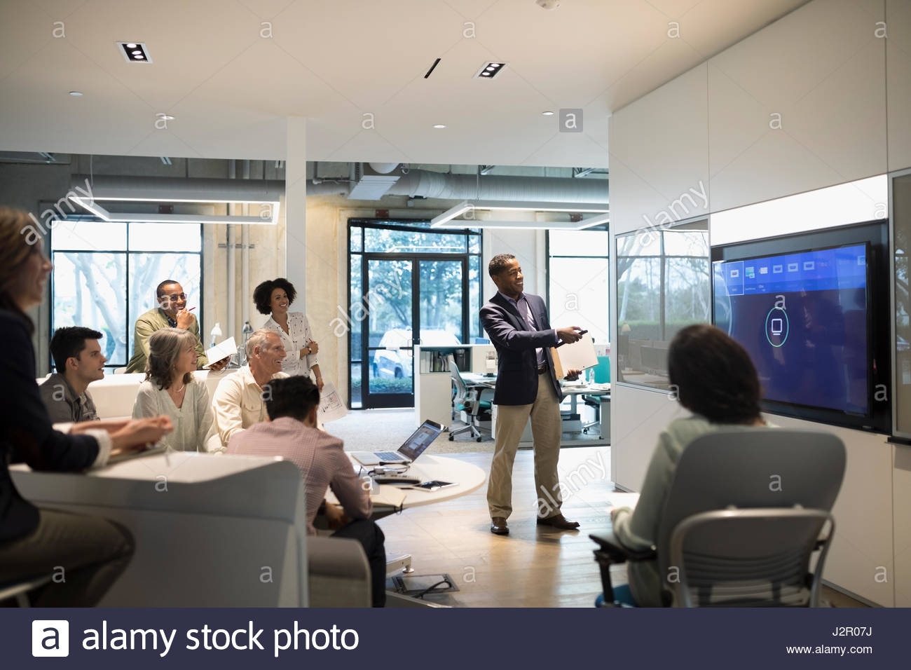 Businessman leading audio visual presentation in conference room meeting - Stock Image