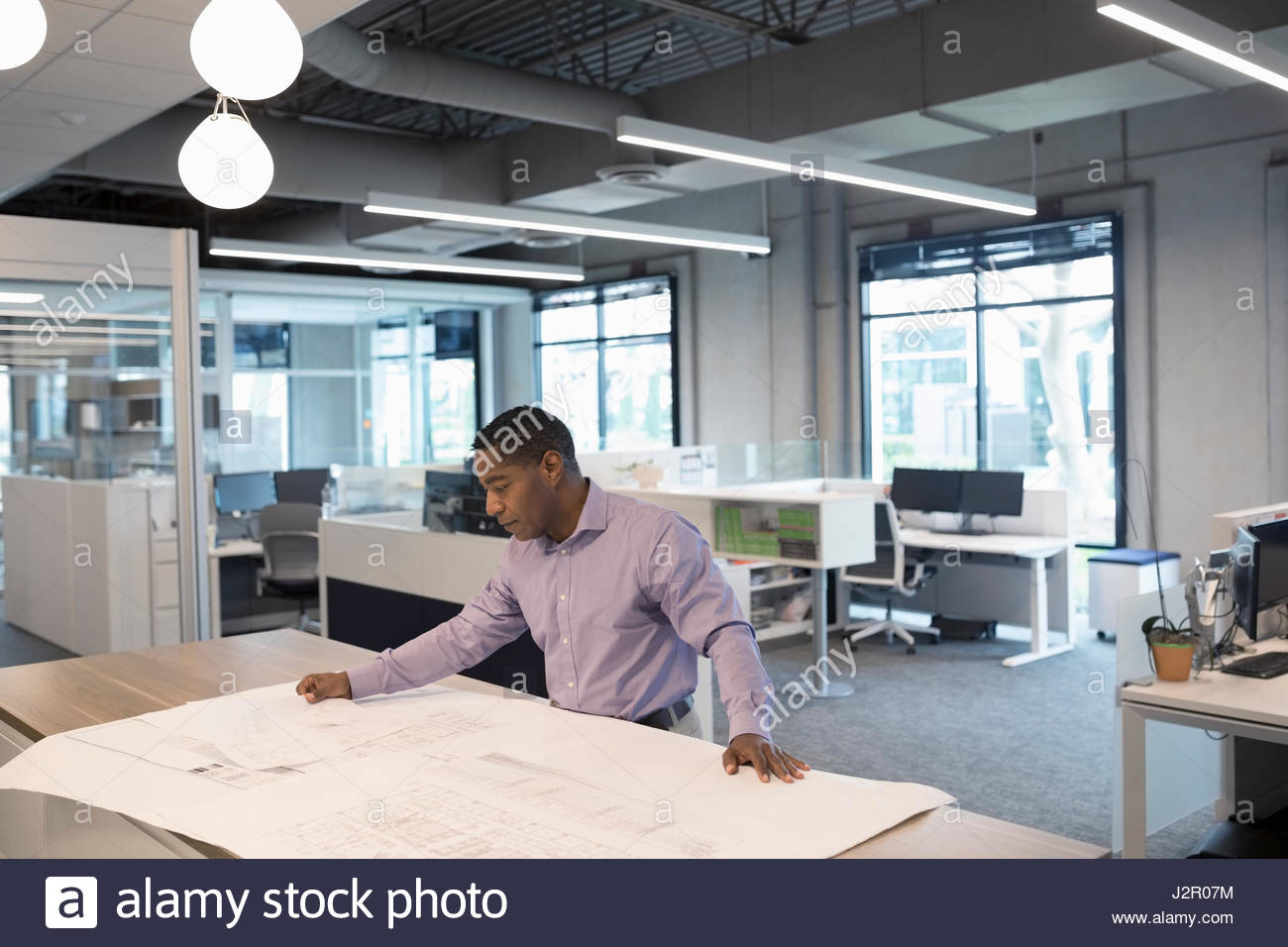 Male African American architect drafting and reviewing blueprints in office Stock Photo