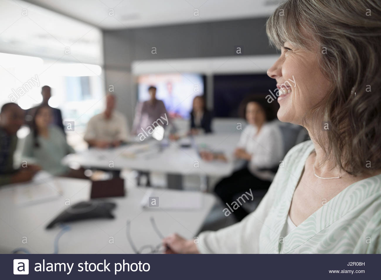Smiling businesswoman leading conference room meeting - Stock Image