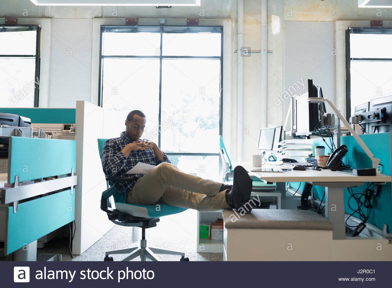 African American businessman working with feet up at office desk - Stock Image