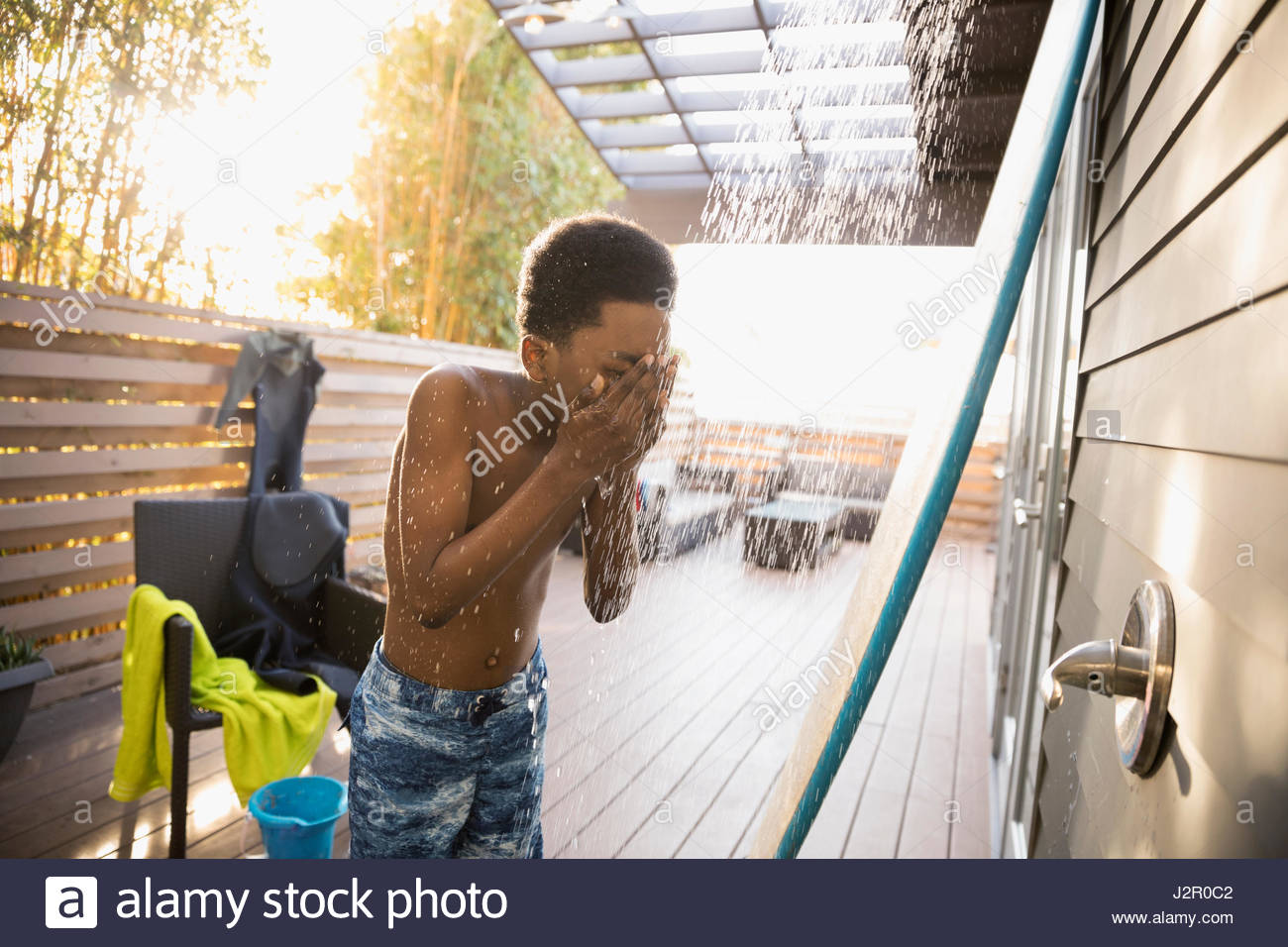 African American boy in swim trunks using beach house shower on deck - Stock Image