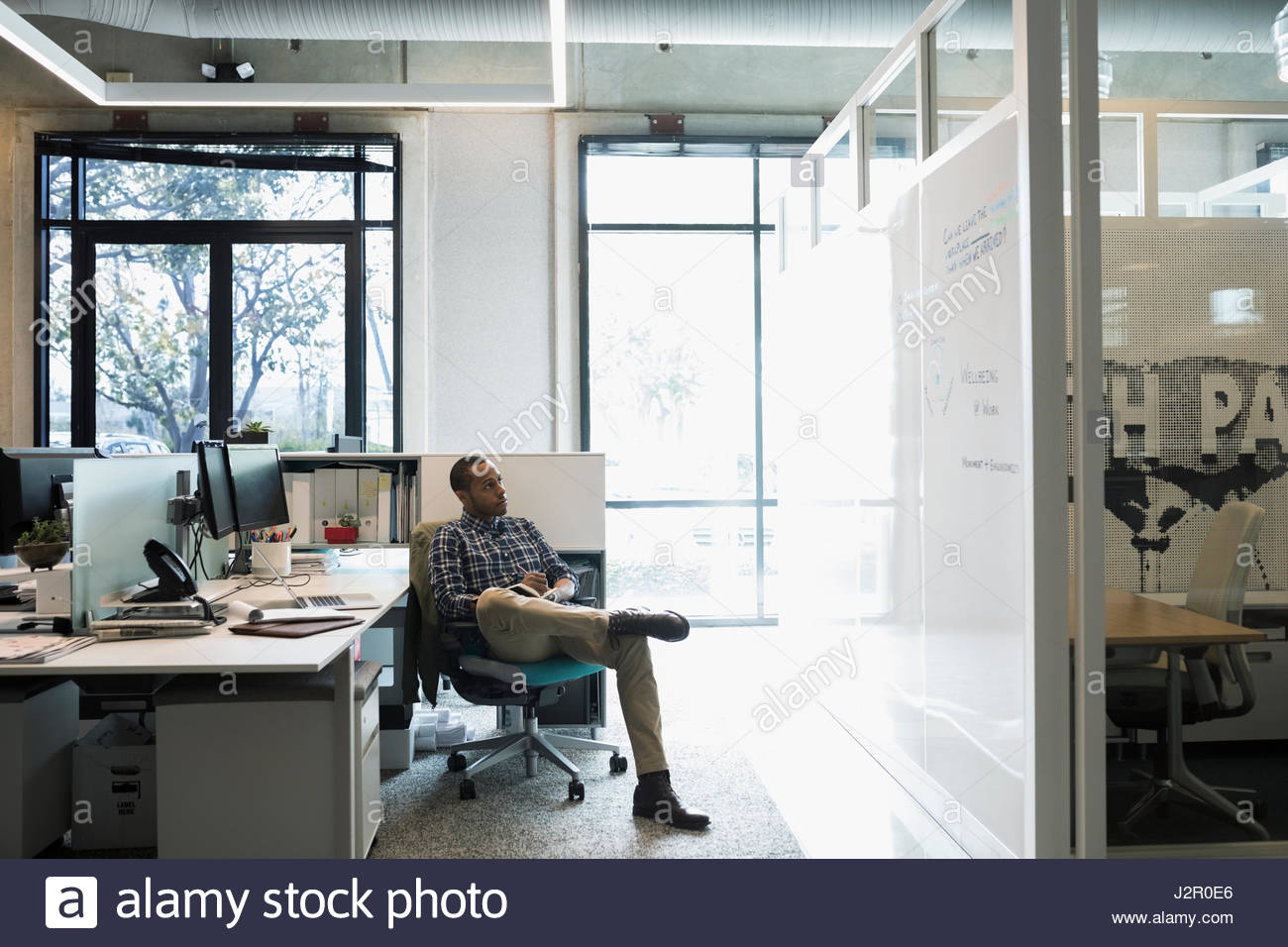 African American businessman working in office cubicle - Stock Image