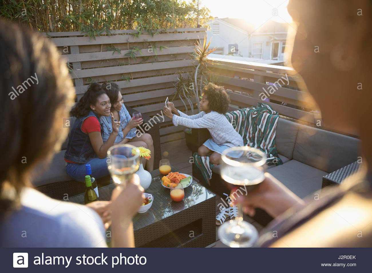 Family hanging out, drinking wine and using digital tablet on sunny deck - Stock Image