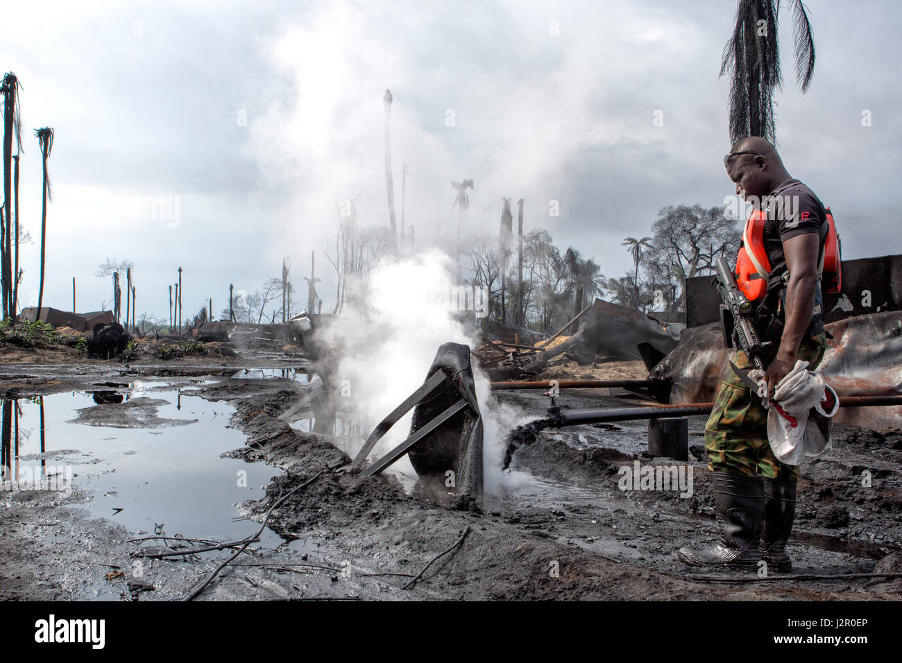 Boiling hot oil is pours into open dikes leading to open air storage pools at the site of an illegal refinery, causing - Stock Image