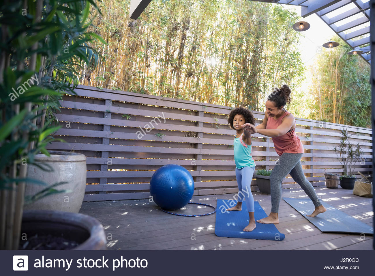 African American mother and daughter practicing yoga warrior 2 pose on deck - Stock Image