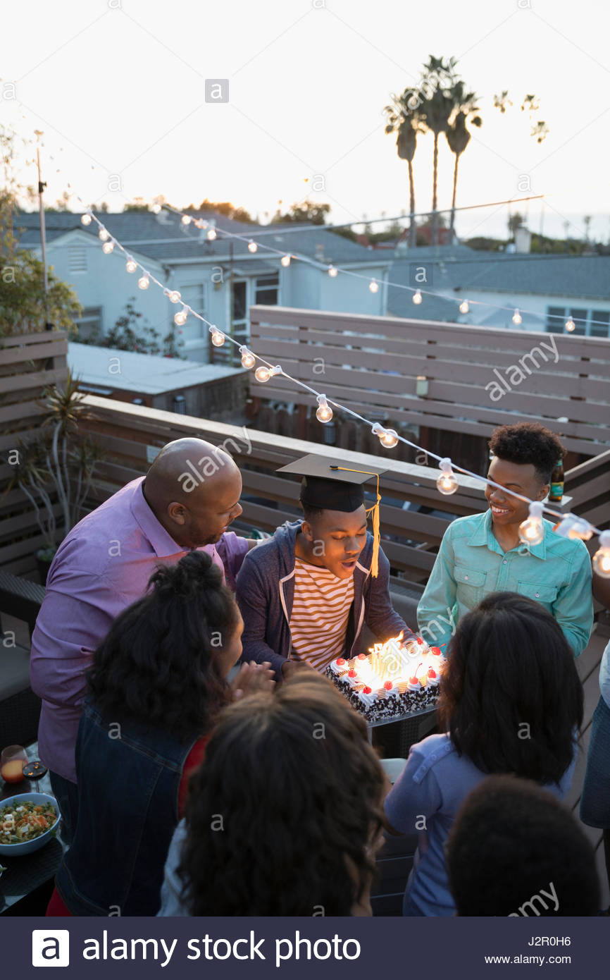 African American family celebrating graduation with cake on summer deck - Stock Image