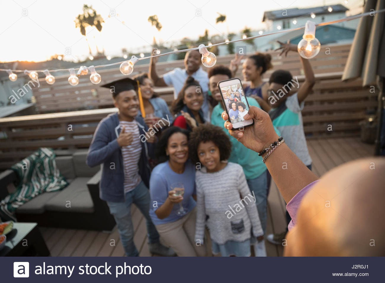 Father with camera phone photographing family celebrating graduation on summer deck - Stock Image
