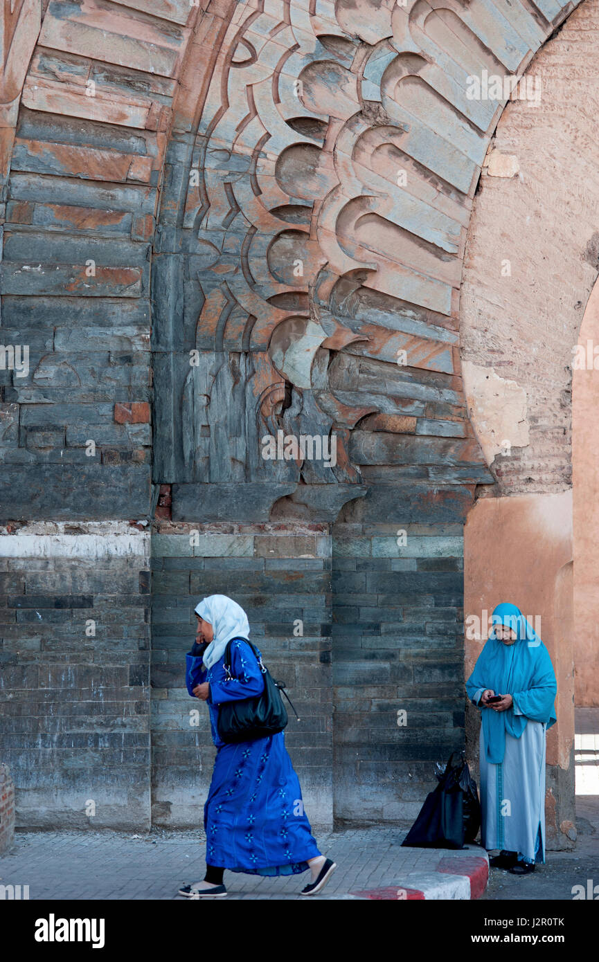 Muslim women in hijabs on mobile phones, Bab Agnaou gate, Marrakesh, Morocco, 2016. - Stock Image