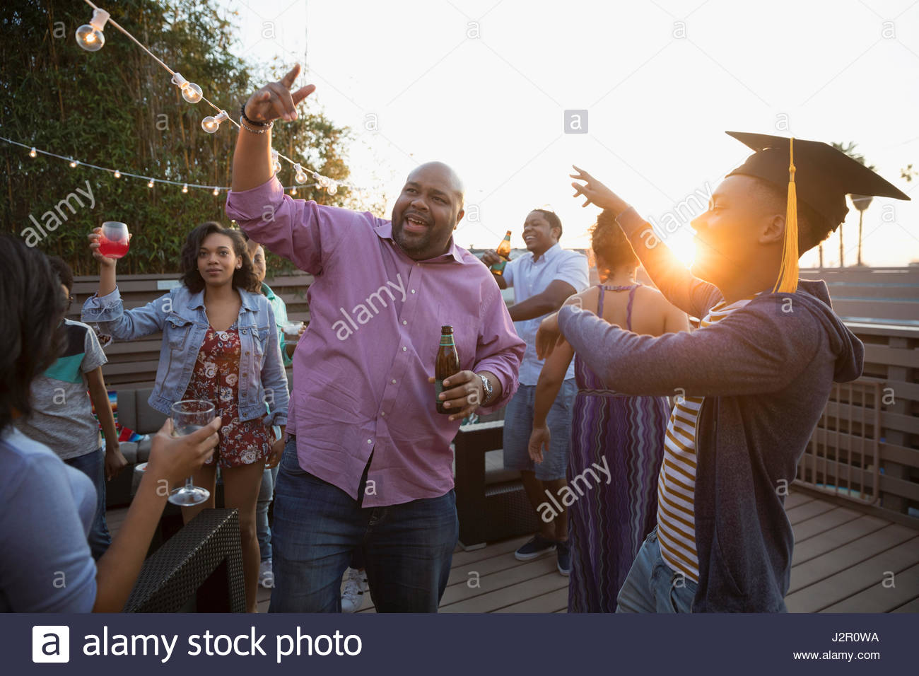 African American father and son celebrating graduation on summer deck - Stock Image