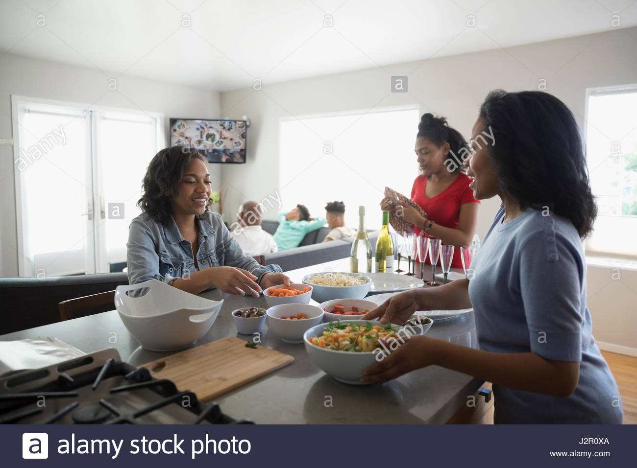 African American mother and teenage daughters cooking in kitchen Stock Photo