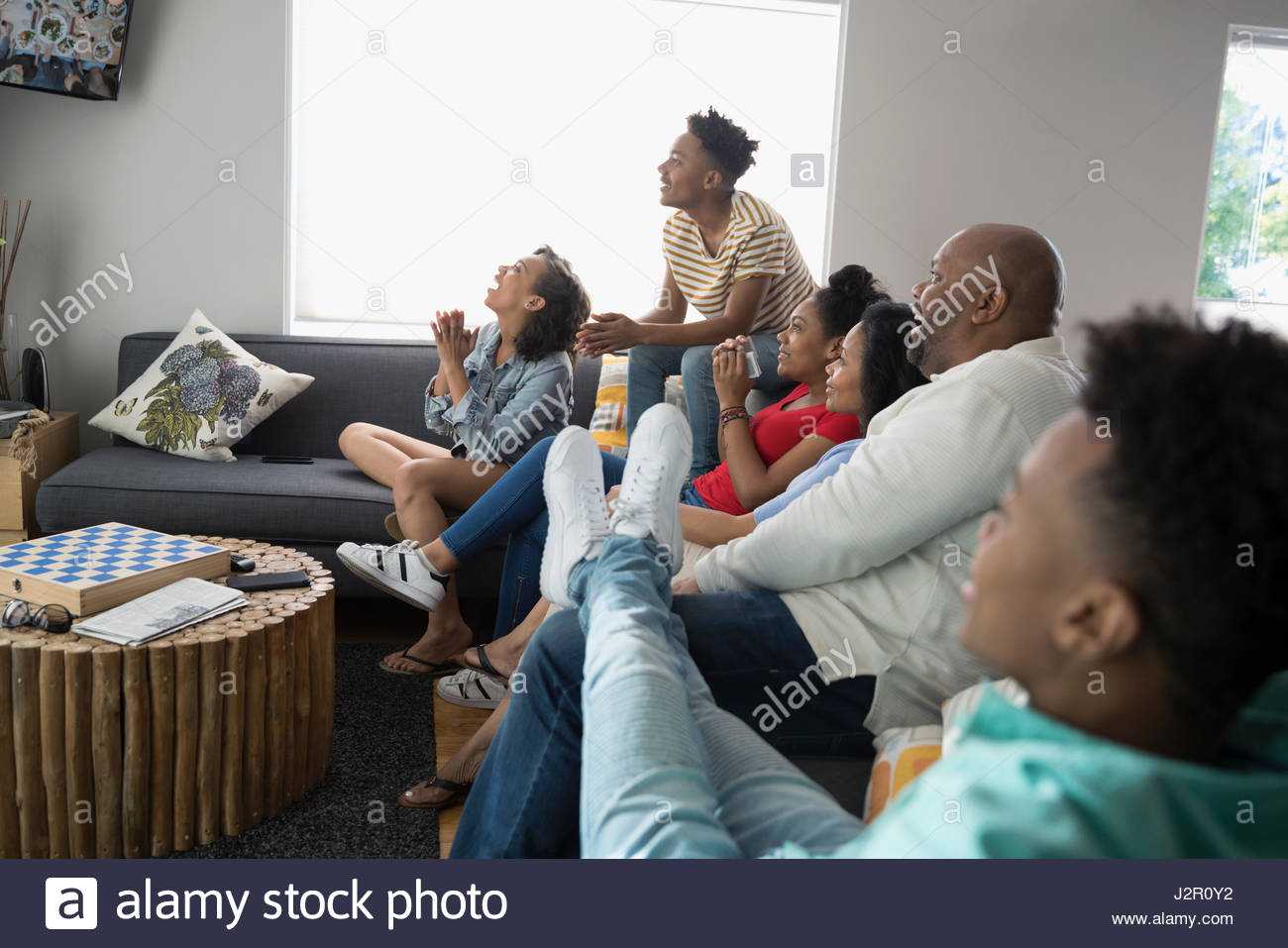 African American family watching TV in living room - Stock Image