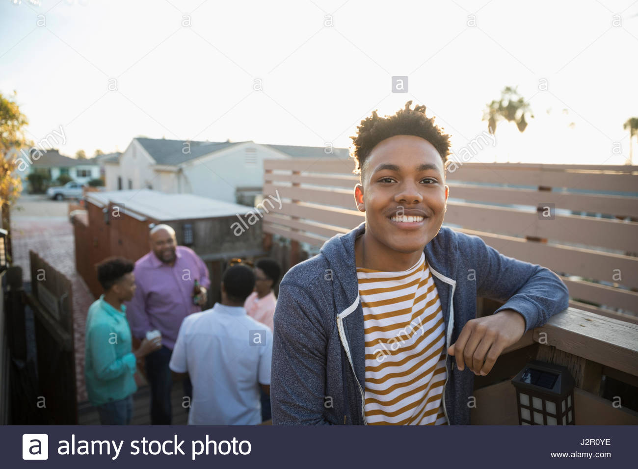 Portrait smiling African American young man on summer deck - Stock Image