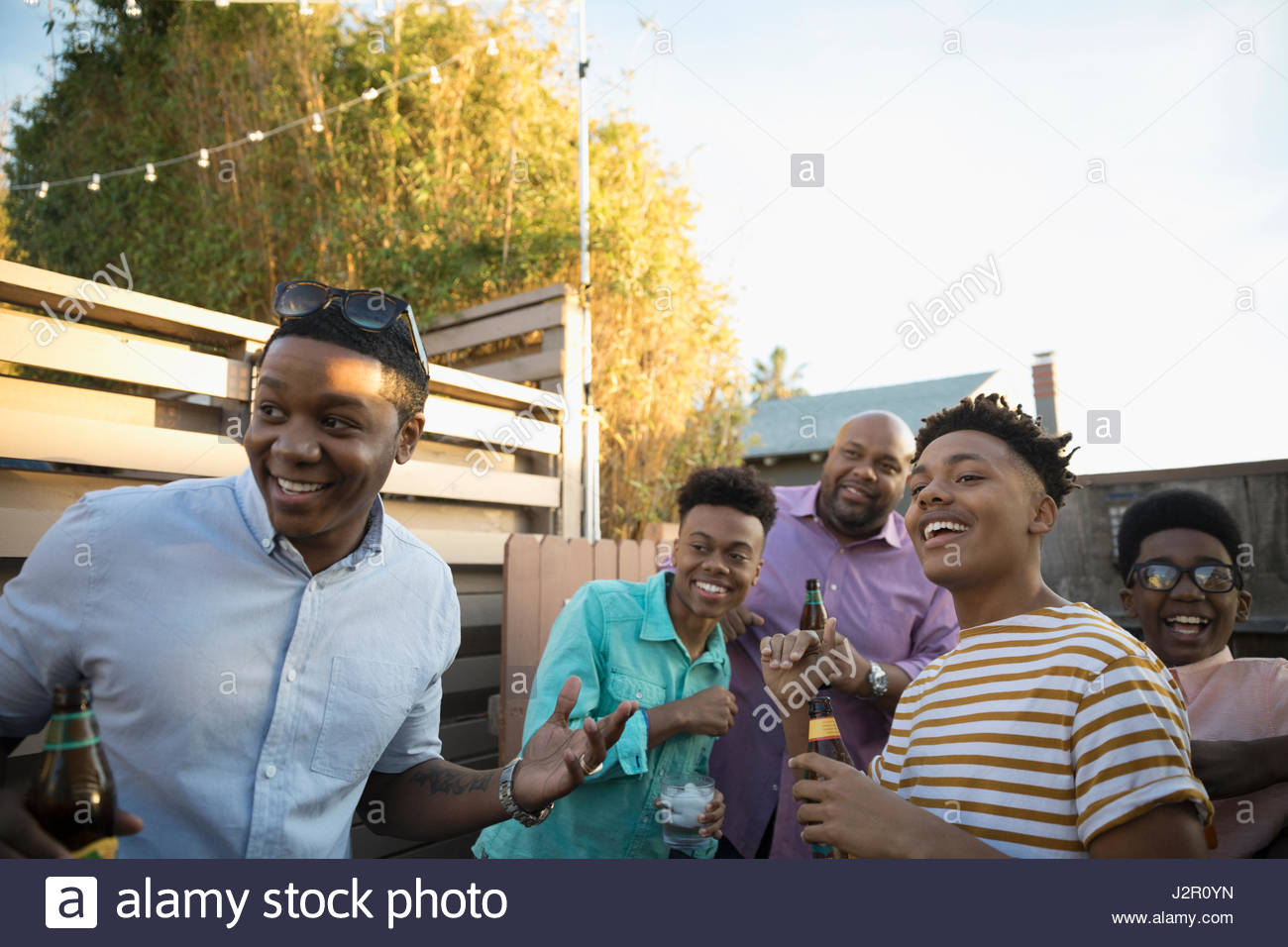 African American family drinking and laughing on summer deck - Stock Image