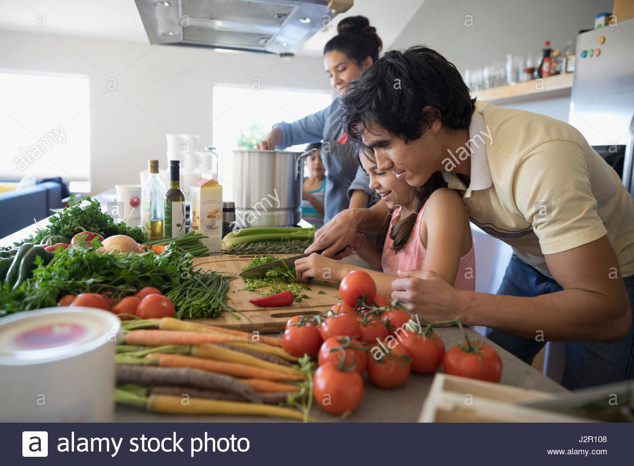 Family cooking, cutting vegetables in kitchen - Stock Image