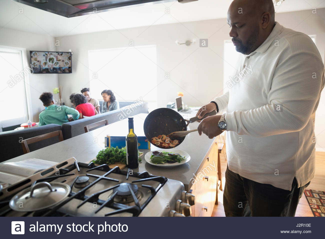African American man cooking in kitchen with family watching TV - Stock Image
