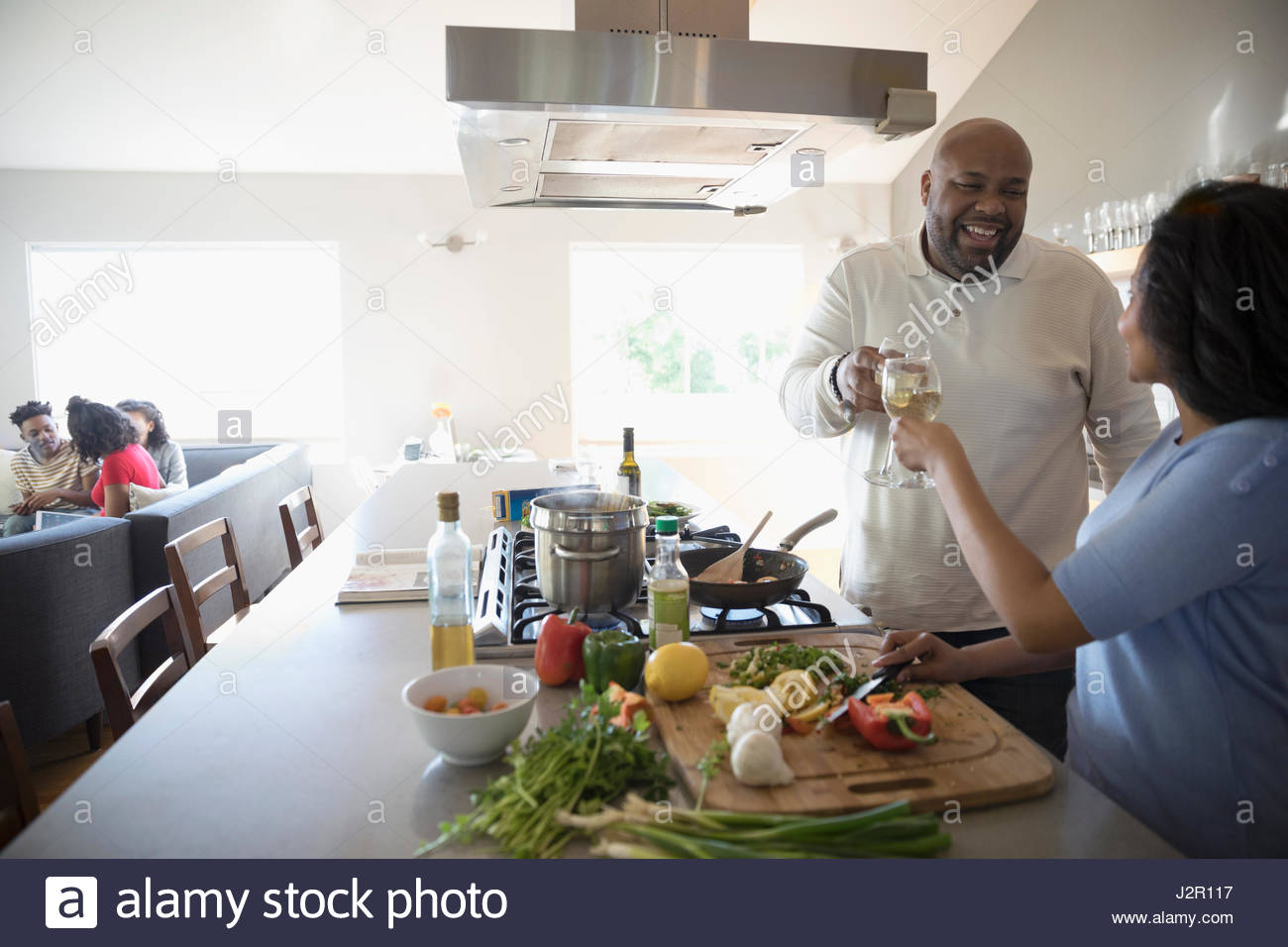 African American couple cooking and drinking white wine in kitchen - Stock Image